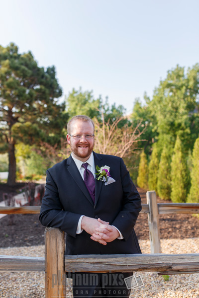 Groom Standing Against Fence With Trees In Background